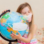 girl in mask hugging a globe
